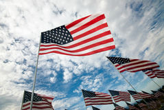 American Flags in rows. Rows of American flags wave in the wind under a blue sky with clouds Royalty Free Stock Photos