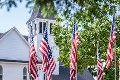 American flags stand solemnly outside church on Memorial Day. Multiple US flags stand outside white church with trees in May Royalty Free Stock Photo
