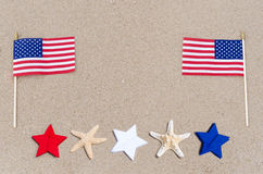 American flags with starfish on the sandy beach Royalty Free Stock Images