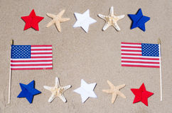 American flags with starfishes on the sandy beach Stock Photo
