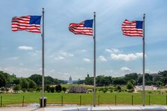American flags at sunny day and Capitol Building in background in Washington DC