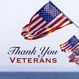 American flags with a Veterans Day greeting. With blue sky baacakground stock photography