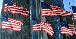 American flags waiving in the wind with skylines in the background showing success. USA flag image of power and freedom Royalty Free Stock Image