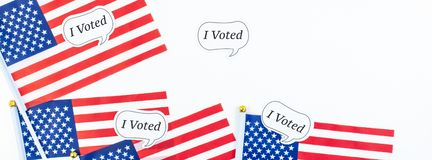 American flags on white background top view. Creative top view flat lay of American flags for Elections stickers I voted with copy space on white background in stock photography