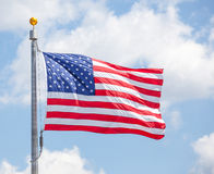 American flap flapping on blue sky. American flap flapping against a blue sky on a flag pole, focus on star of waving flag Stock Image