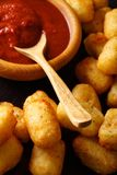 American food: tater tots and ketchup close-up. Vertical. American food: tater tots and ketchup close-up on the table. Vertical Royalty Free Stock Image