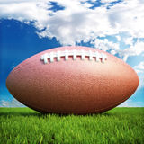 American football. On a grass field with a sky background , room for text or copy space Royalty Free Stock Photo
