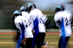 American football abstract blur. Four american football players running together - abstract blur Royalty Free Stock Images