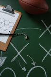 American Football And Referee Whistle Lying On Green Board With Strategy Drawn On It