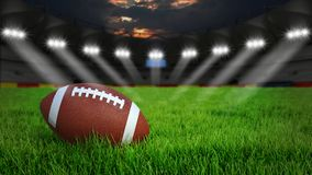 American football stadium. American football arena with ball on green grass illumination at night, 3D rendering Stock Image