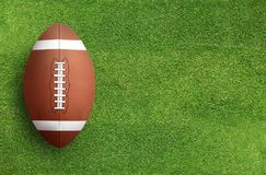 American football ball on grass field background. American football ball on green grass field background. Football ball 3D illustration stock photography