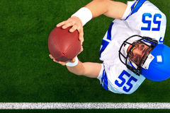 American football catching the ball. Overhead photo of an American football player wide receiver catching the ball in the air. The uniform he's wearing is one I Royalty Free Stock Photos