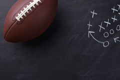 American Football on Chalkboard. Top view of an American style football on a chalkboard with a play diagramed. Horizontal format with copy space Stock Photography