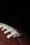 American football closeup. Close up of a football over black Stock Photos