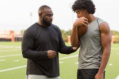 American Football coach training a young athlete. American Football coach teaching and training a young athlete stock photography