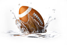 American football falling into clear water, forming a crow Royalty Free Stock Photos
