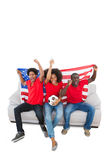 American football fans in red cheering on the sofa Royalty Free Stock Photography