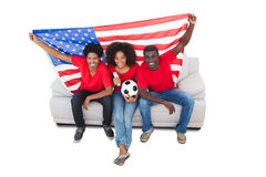 American football fans in red on the sofa Stock Image