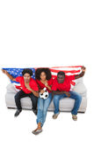 American football fans in red on the sofa Royalty Free Stock Photography