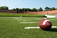 American Football on Field. Closeup of American football on field with goal post in background.  Field level view Stock Photography