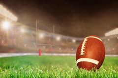 Outdoor Football Stadium With Ball on Grass and Copy Space. American football on field grass in brightly lit outdoor stadium with focus on foreground and shallow Royalty Free Stock Photos