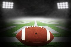 American Football on Field With Rising Fog and Dramatic Lighting. Close up of American football on stadium field with yard line markings and dramatic spotlight stock illustration