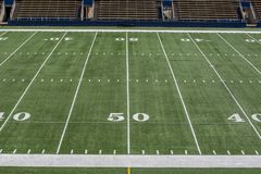 American football field with 50 yard line. Horizontal image of American football field with stadium seating, green astroturf and fifty yard line Royalty Free Stock Photography