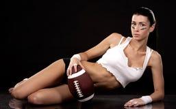 American football girl. Athletic brunette posing as american football girl on black background Royalty Free Stock Photo
