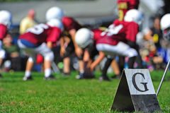 American Football goal line. Abstract of American youth football goal marker on the line with out of focus players in the background playing the game Stock Photo