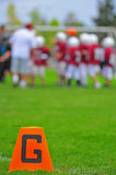 American Football goal marker. Abstract of American youth football orange cone goal marker with players in the background talking to the coach Royalty Free Stock Images
