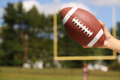 American Football in Hand over Field royalty free stock images