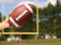 American Football in Hand over Field with Goal Post Stock Image