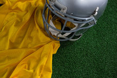 American football head gear and jersey lying on artificial turf Stock Photos