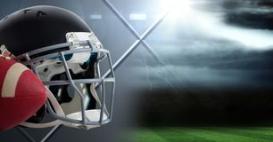 American football helmet and ball with field transition. Digital composite of American football helmet and ball with field transition Royalty Free Stock Images