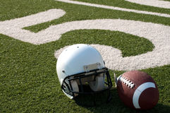 American Football and Helmet on Field Royalty Free Stock Images