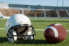 American Football and Helmet on Field. With goal post in background Stock Image