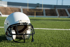 American Football  Helmet on Field. With goal post in background Royalty Free Stock Photo