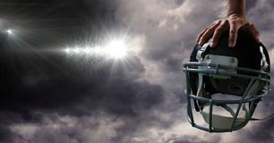 American football helmet in hand with stadium transition. Digital composite of American football helmet in hand with stadium transition royalty free stock images