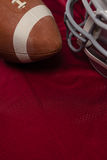 American football and helmet on jersey. High angle view of helmet and American football on red jersey Royalty Free Stock Photos