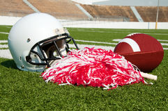American Football, Helmet, and Pom Poms. On field in stadium Royalty Free Stock Photography