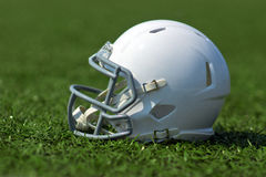 American football helmet. White american football helmet at artificial turf in the playing field Royalty Free Stock Photography