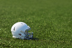 American football helmet. White american football helmet at artificial turf in the playing field Royalty Free Stock Photo