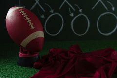 American football jersey and football lying on artificial turf against strategy board Stock Images