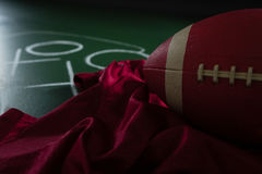 American football jersey and football lying on green board with strategy drawn on it Stock Image