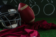 American football jersey, head gear and football lying on artificial turf against strategy board Stock Photo