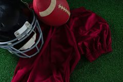 American football jersey, head gear and football lying on artificial turf Stock Photos