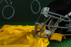 American football jersey and head gear lying on artificial turf against strategy board Royalty Free Stock Photography