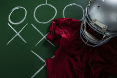 American football jersey and head gear lying on green board with strategy drawn on it Royalty Free Stock Photo