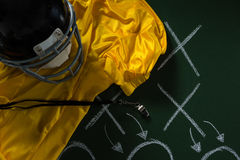 American football jersey, referee whistle and head gear lying on green board with strategy drawn on Stock Photography