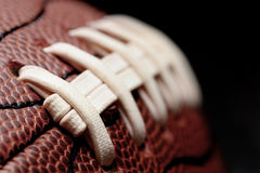 American football macro. American football - macro over black with shallow depth of field and focus on first seam